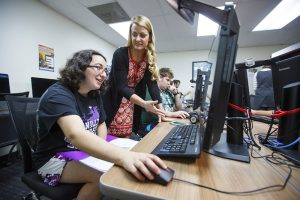 Student and Teacher interacting by computer